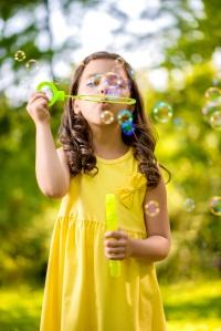 Little girl blowing soap bubble