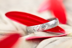 Silver ring with engraved hearts and flower petals.
